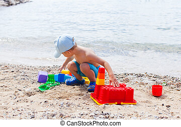 Small child is playing with sand on the beach