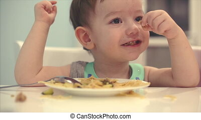 Small child is sitting at a table in a bib and eat his own spaghetti, the baby eats willingly.