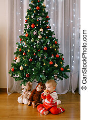 Small child is snacking on an apple in front of a Christmas tree with her stuffed toys under it