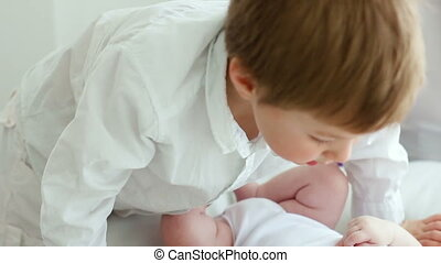 small child kissing a newborn baby brother