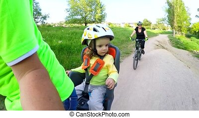Small Child On Bike Backseat Enjoying The Trip Together With Parents In Green Park