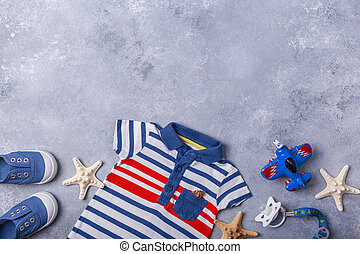 Small child or baby boy accessories on grey background travel with baby concept