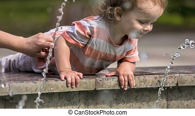 Small Child  Playing With Water In Fountain