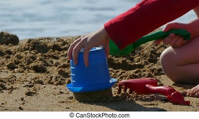 small child plays on the beach with toys for sand