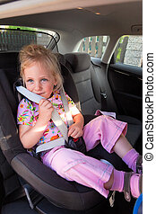 child sitting in the car seat in the car