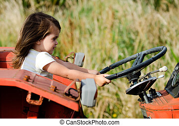 Small child sitting on an old tractor