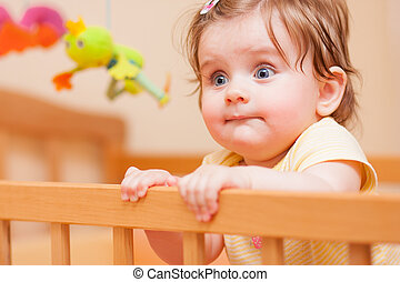 small child with a hairpin standing in crib