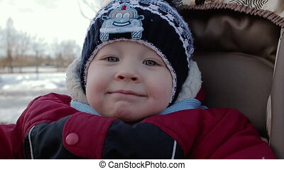 Small child with expressive eyes looks at the camera and smiles.