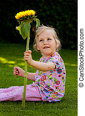 child with sunflower in the garden