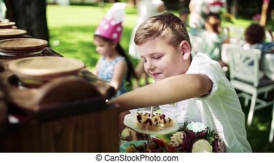 Small children outdoors on garden party in summer, eating...