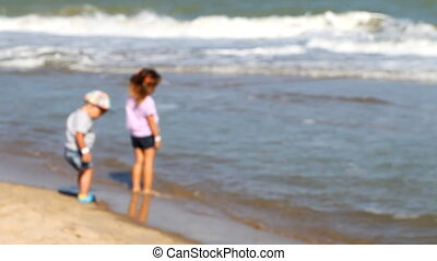 small children play on the beach