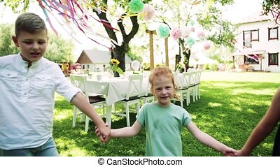 Small children playing outdoors on garden party in summer. ...