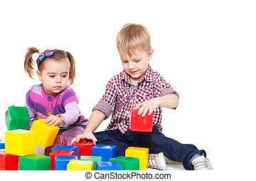Small children sit on a floor and play with multi-coloured...