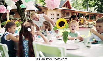 Small children sitting at the table outdoors on garden party...