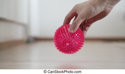 small children's pink rubber studded ball jumping at home in...