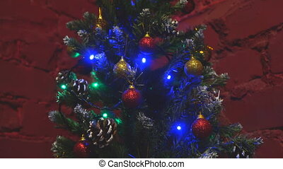 Small Christmas tree decorated with Christmas toys on the background of a red brick wall