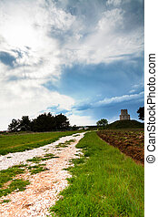 Small church on top of a hill with clouds