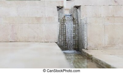 Small city fountain - water falling on marble steps, close...