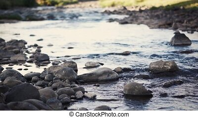 small clean river in uplands - river valley with stones and...