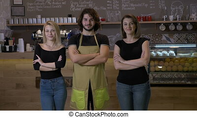Small coffee shop business owners and staff wearing apron...