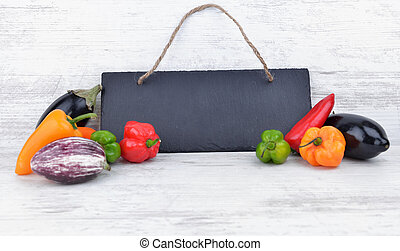 small colorful hot peppers and aegplants  each other of a black slate on  white table