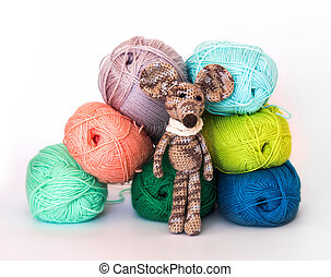 small colorful knitted toy mouse in a white scarf playing with colored yarn, threads of wool, Bright children's toy, clew, knitted mouse between skeins