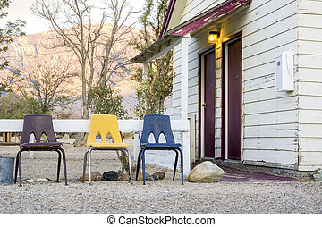 Small cottage house with 3 chairs in front of it.