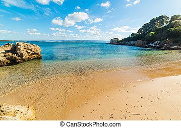 Small cove in Alghero shoreline on a sunny day