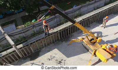 crane lifts part of wall and carries it, several workers are...