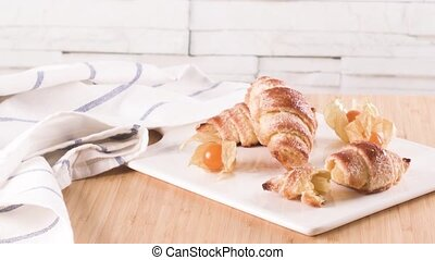 Small croissant with physalis fruits in white ceramic tray,...