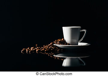 Small cup of black coffee on a dark background with coffee beans