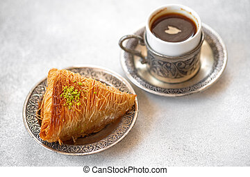 Small cup of Turkish coffee and Turkish baklava on table