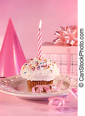 Small cupcake with candle, gift and pink party hat
