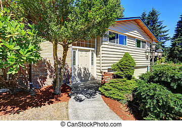 Small cute American house with green shrubs.