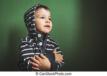 small cute baby boy crossing hands in pullover