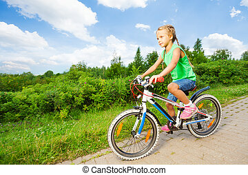 Small cute girl riding children bike on road