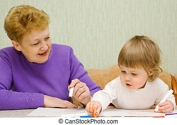 Small cute painting girl with grandma at home