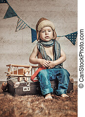 Small, cute pilot with a wooden plane