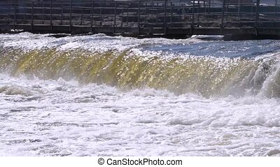 small dam across the river close. Powerful flow of water and white foam. Ukraine