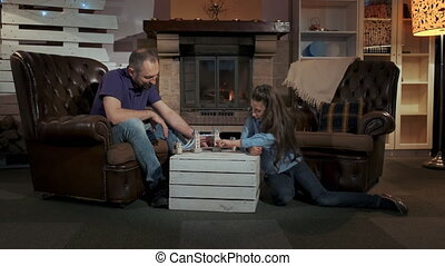 Small daughter and father playing together in a big comfortable living room near the fireplace