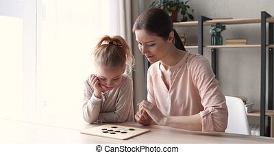 Small 6-7 years daughter and young mom playing checkers at home table. Cute child girl having fun with mother or nanny enjoying draughts board game. Parent and kid leisure hobbies activities concept