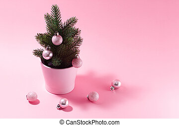 Small decorative Christmas tree on a pink background.
