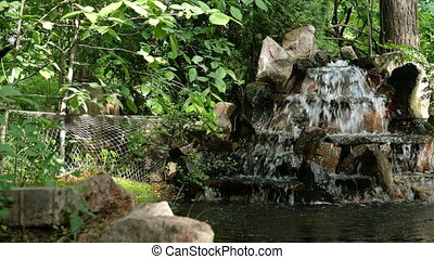 Small decorative fountain or waterfall of stones, flows into a decorative pond, in garden.
