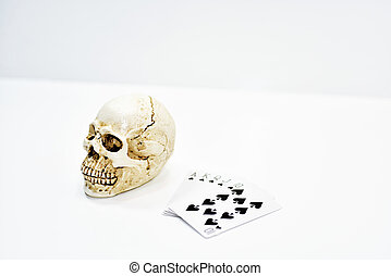 Small decorative human skull with playing cards.