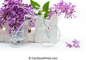 Small decorative white bicycle on a background of purple flowers lilac