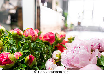 Small family business. In the foreground a bouquets of peonies on the background of a flower shop. People work, Profession florist. Summer bouquet. Flowers delivery