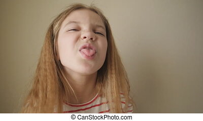 Small female child sticking her tongue out and turning aside indoor. Little girl with long blonde hair showing displeased emotion into camera. Cute kid fooling around against the background of wall