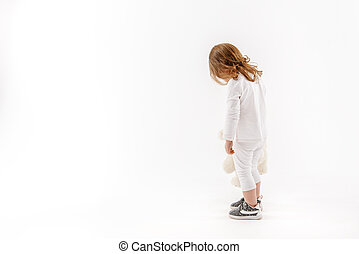Lost child is holding toy. Sad Girl standing with her back to camera and head down. Isolated and copy space in left side