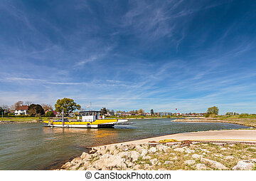 Small ferry crossing the Dutch river IJssel in front of the...
