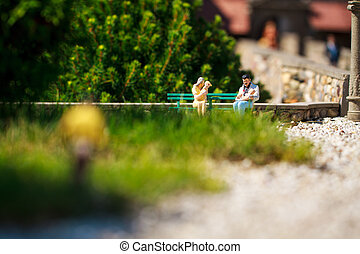 Small figurines of family sitting on bench in garden.